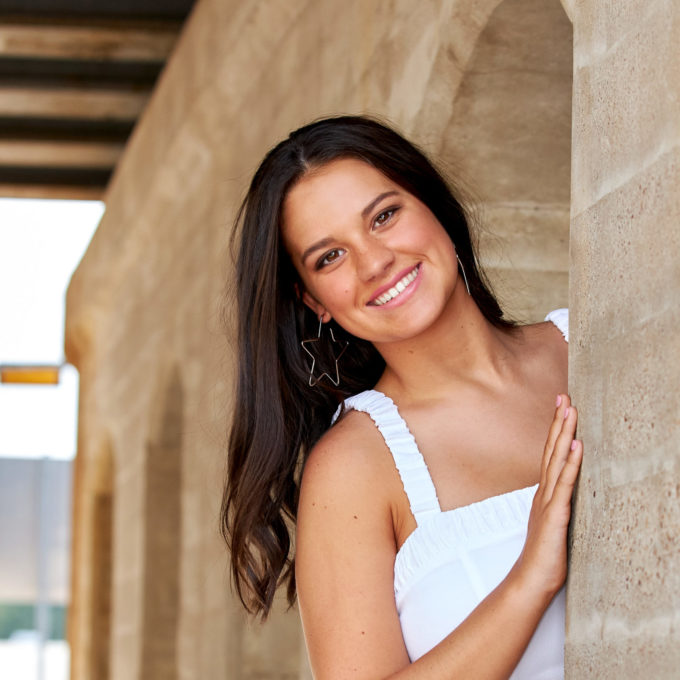 Girl peaking from side of wall smiling